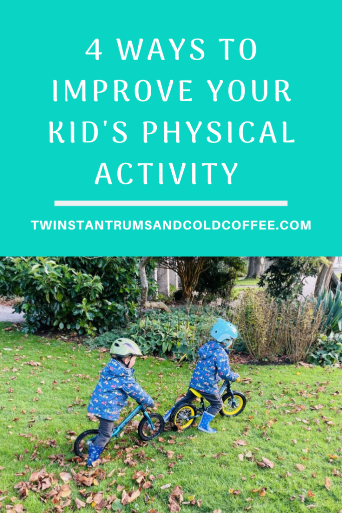 Twin three year old boys on balance bikes on grass as a way to improve your kid's physical activity