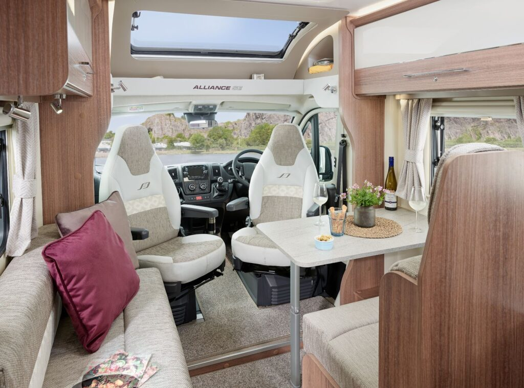 The front part of a motorhome showing the dining, living area and drivers seat