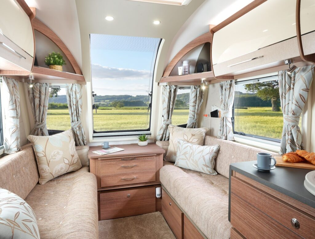 Inside a caravan showing the settee and living area you'd have on a caravan holiday