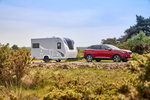A red car towing a caravan in the countryside going on a caravan holiday