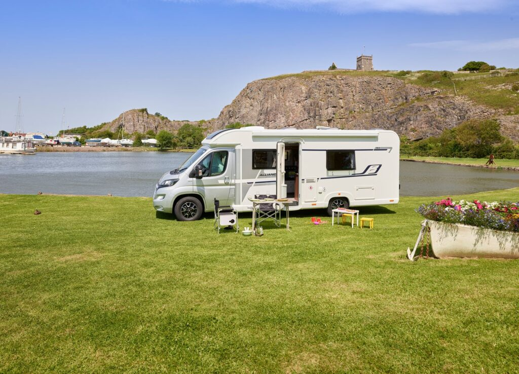 A Bailey motorhome parked next to a lake and castle