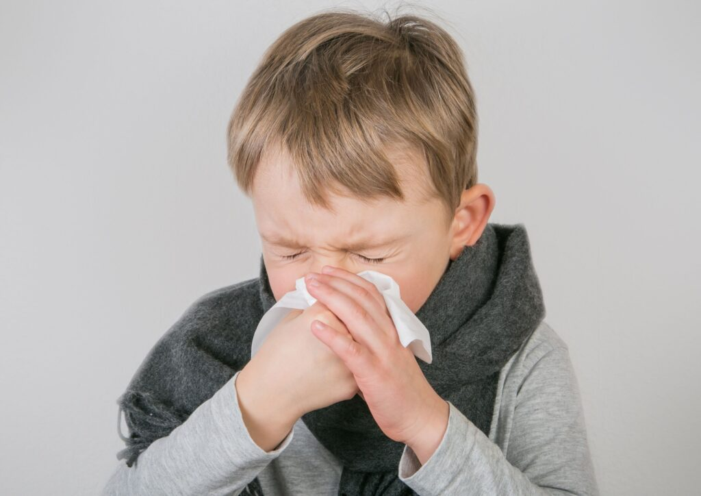 Little boy blowing his nose into a tissue