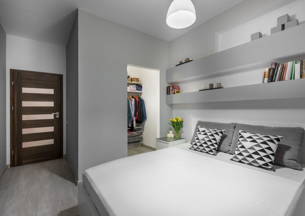White bed against grey walls and shelves in a bedroom