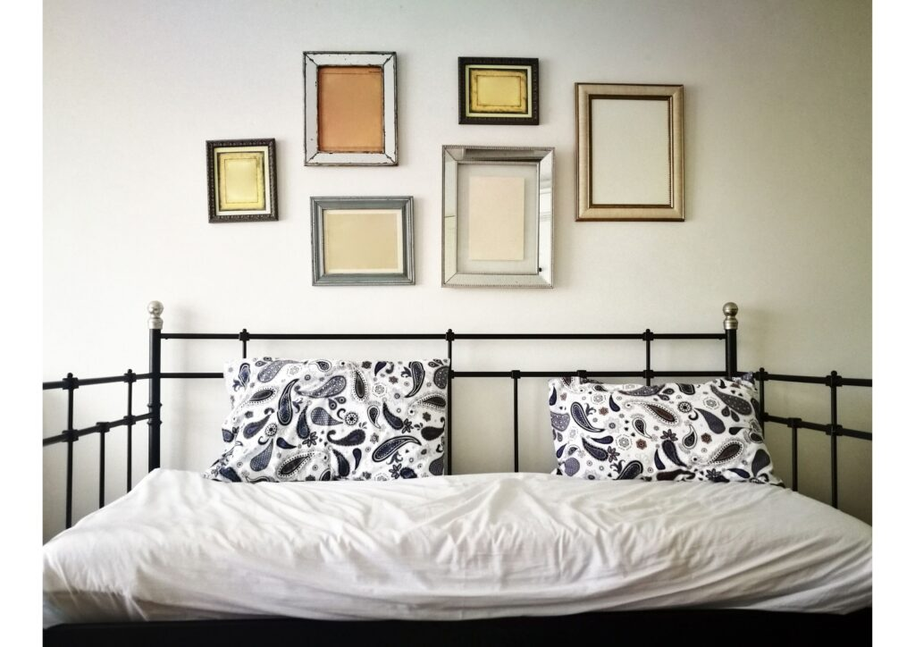 photo frames on a wall of a spare room over a sofa bed