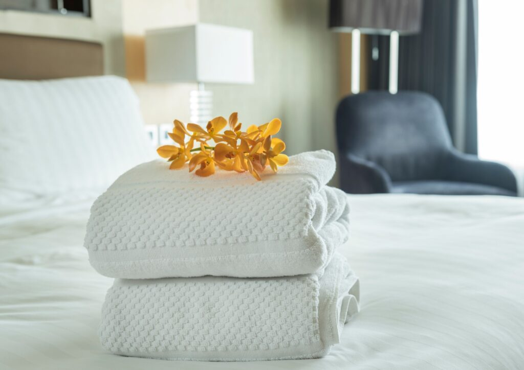 A set of folded white towels with flowers on the top on a bed in a spare room for guests