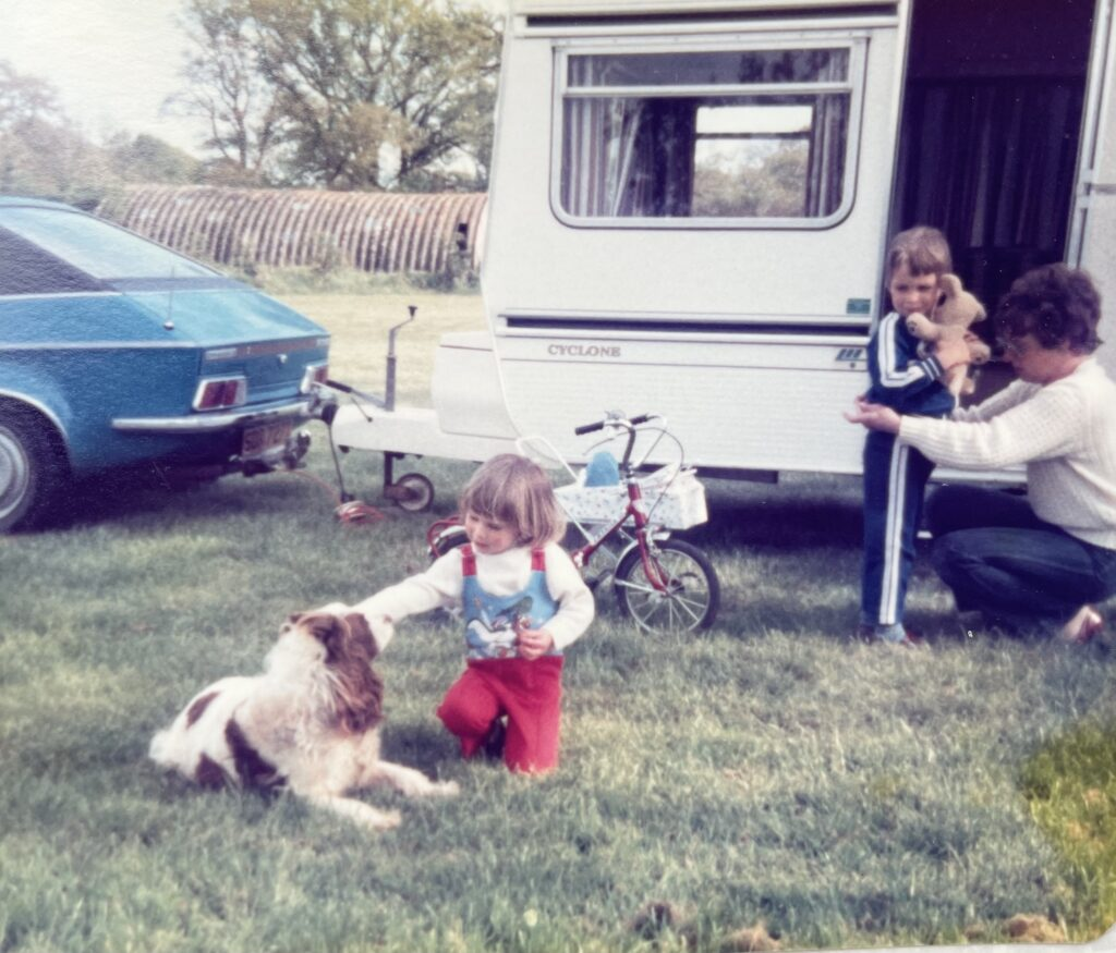 Old pic of a little girl about 2 playing with a dog outside a caravan