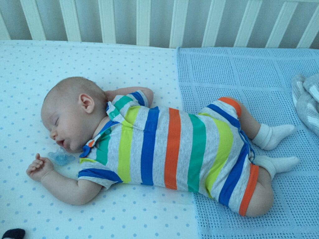 Baby wearing a stripy romper asleep in his cot