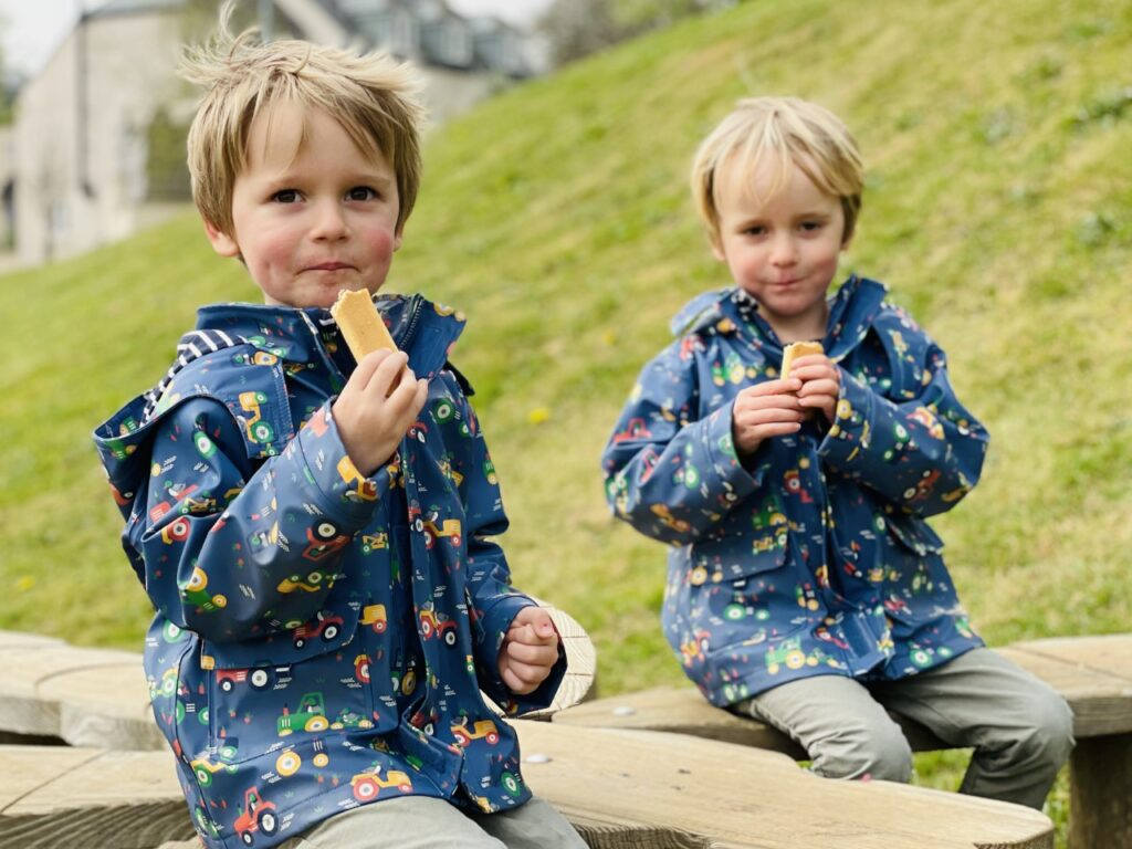 Potty training twins doesn't mean they're both ready at the same time.Twin boys on a park bench eating a biscuit.