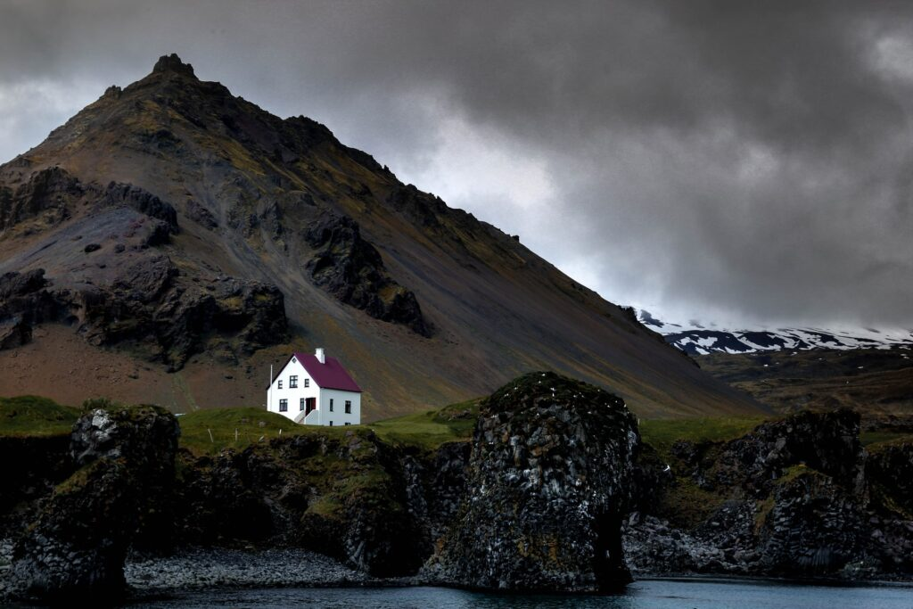 A stormy sky over a mountain and a lone white house in Westfjords in Iceland