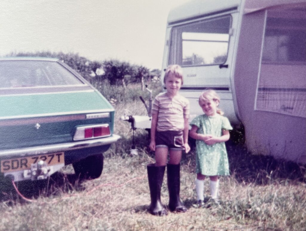 Old picture of a brother and sister aged about 6 and 3 stood outside a touring caravan