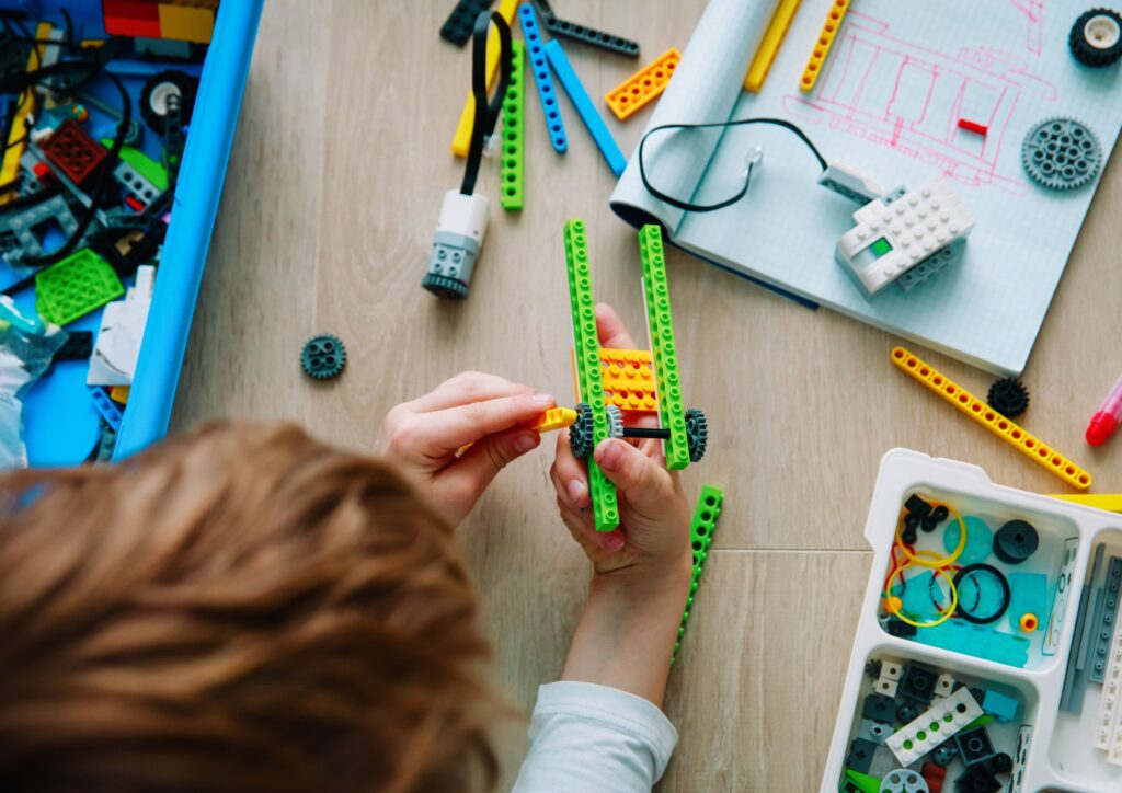 Overhead shot of a boy building lego at a desk as a technology and STEM subject