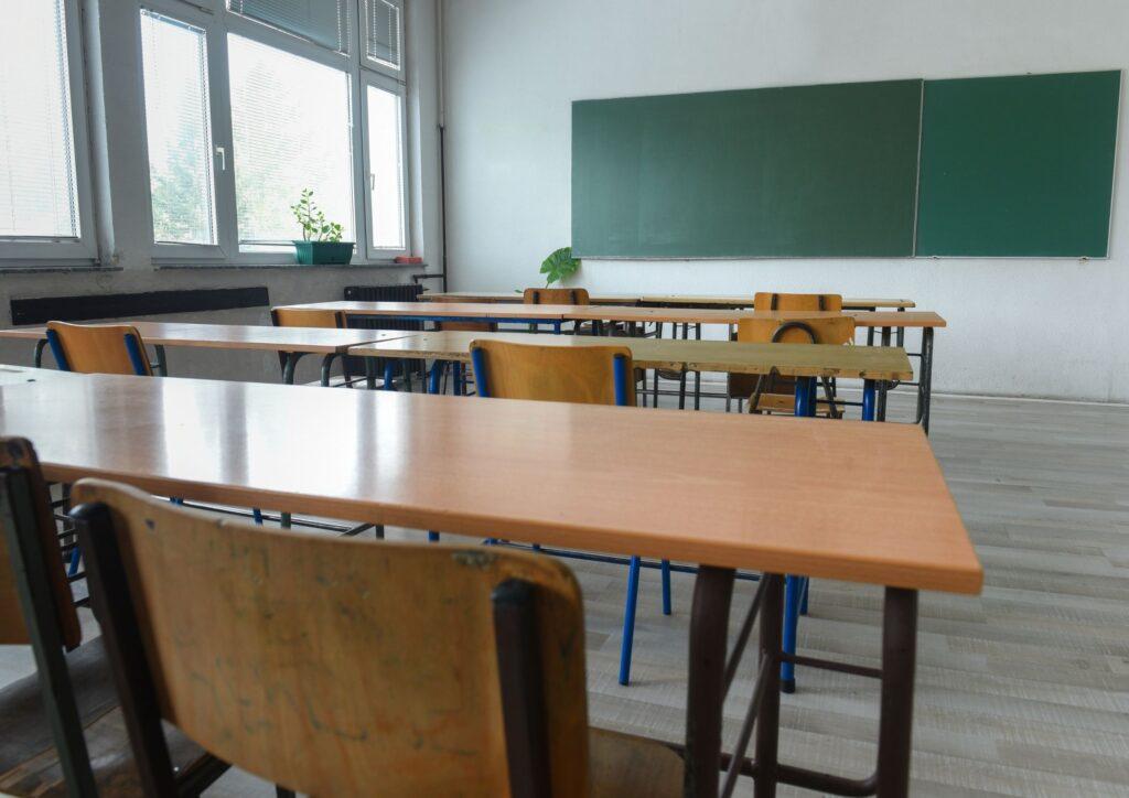 Desks in a classroom in front of a blackboard