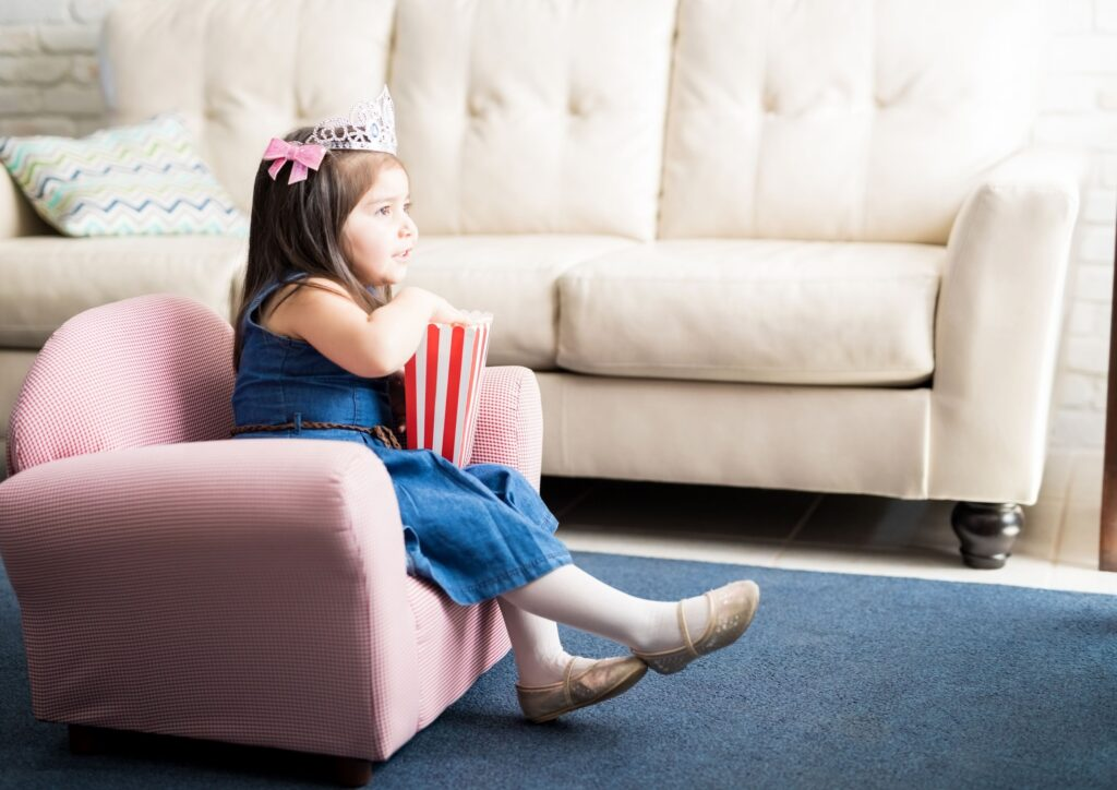 Little girl eating popcorn sitting in a chair watching a kids movie on TV