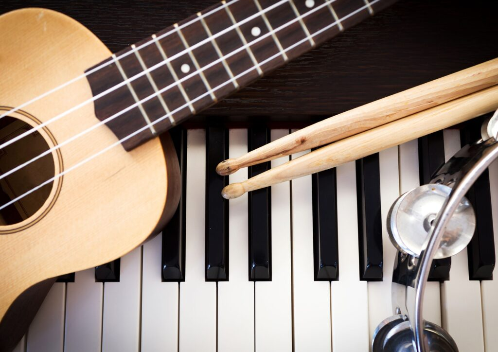 A piano with a guitar, tambourine and drumsticks resting on top of it