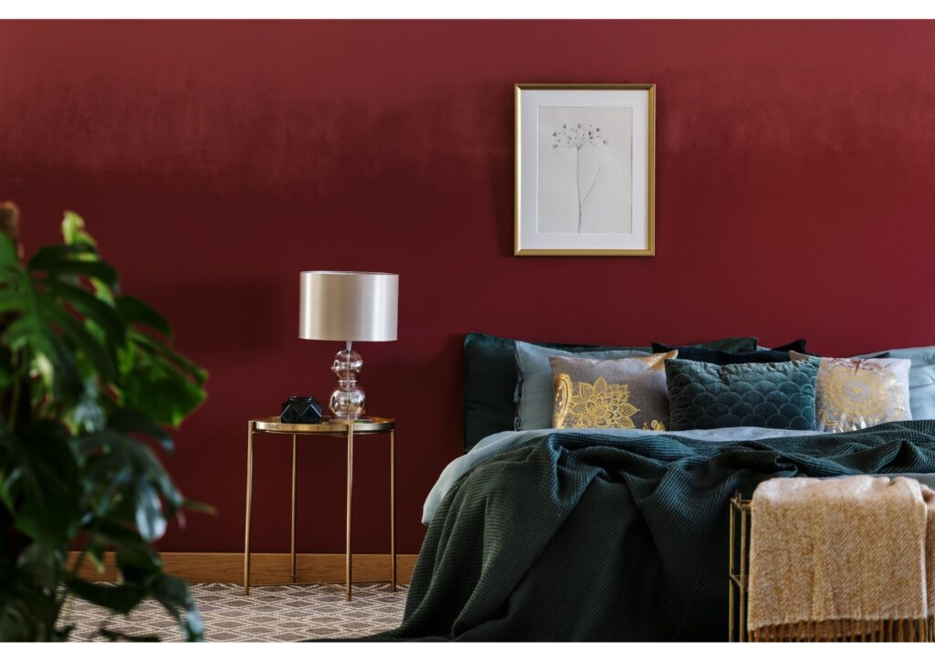 A luxurious bedroom with dark red walls and black bedding with a lamp next to the bed
