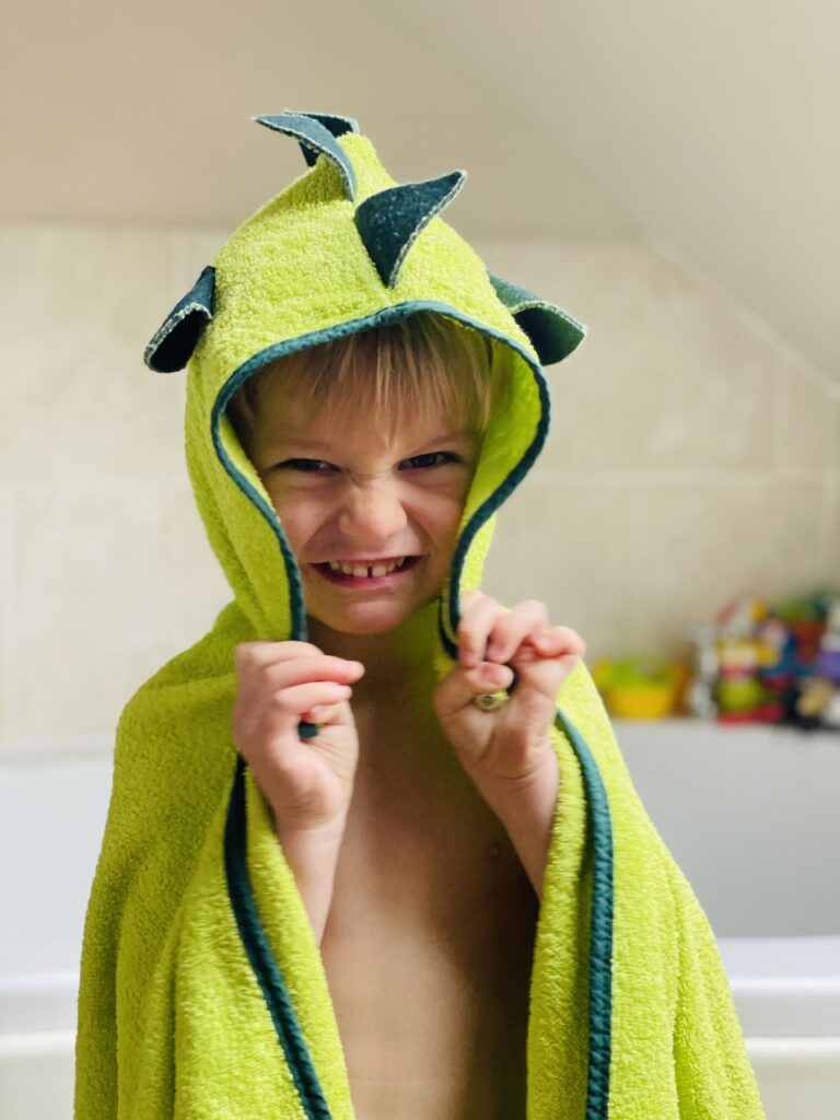 Three year old boy pretending to be a dinosaur in a dino hooded towel