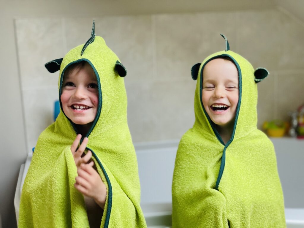 Twin three year old boys next to the bath wearing Cuddledry dinosaur hooded towels