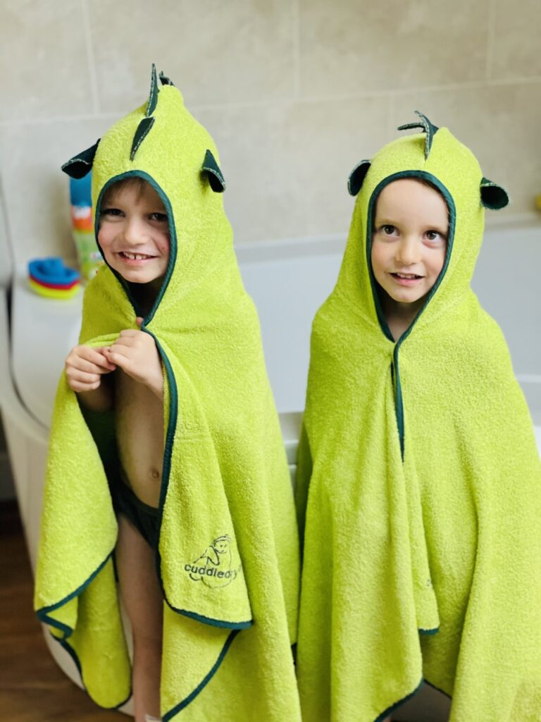 Three year old twin boys wearing Cuddledry hooded towels after a bath