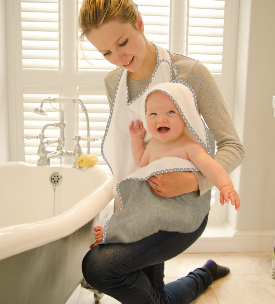 Mum wears a Cuddledry hands free towel to dry her baby off after the bath