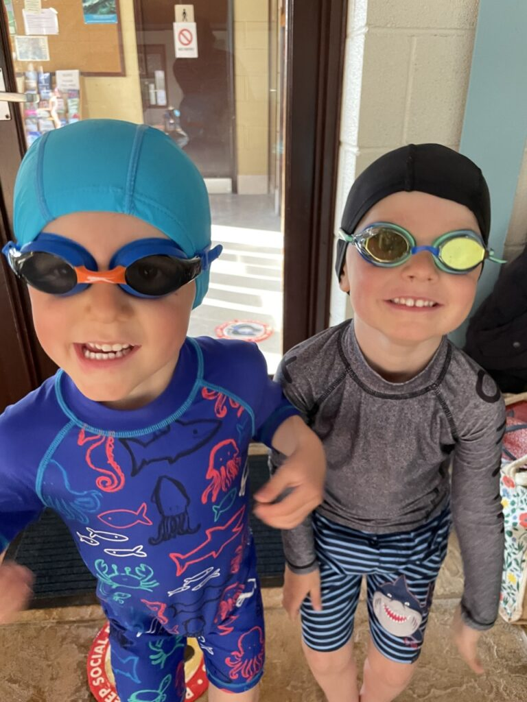 Twin brothers wear swimming costumes, hats and goggles before their lesson