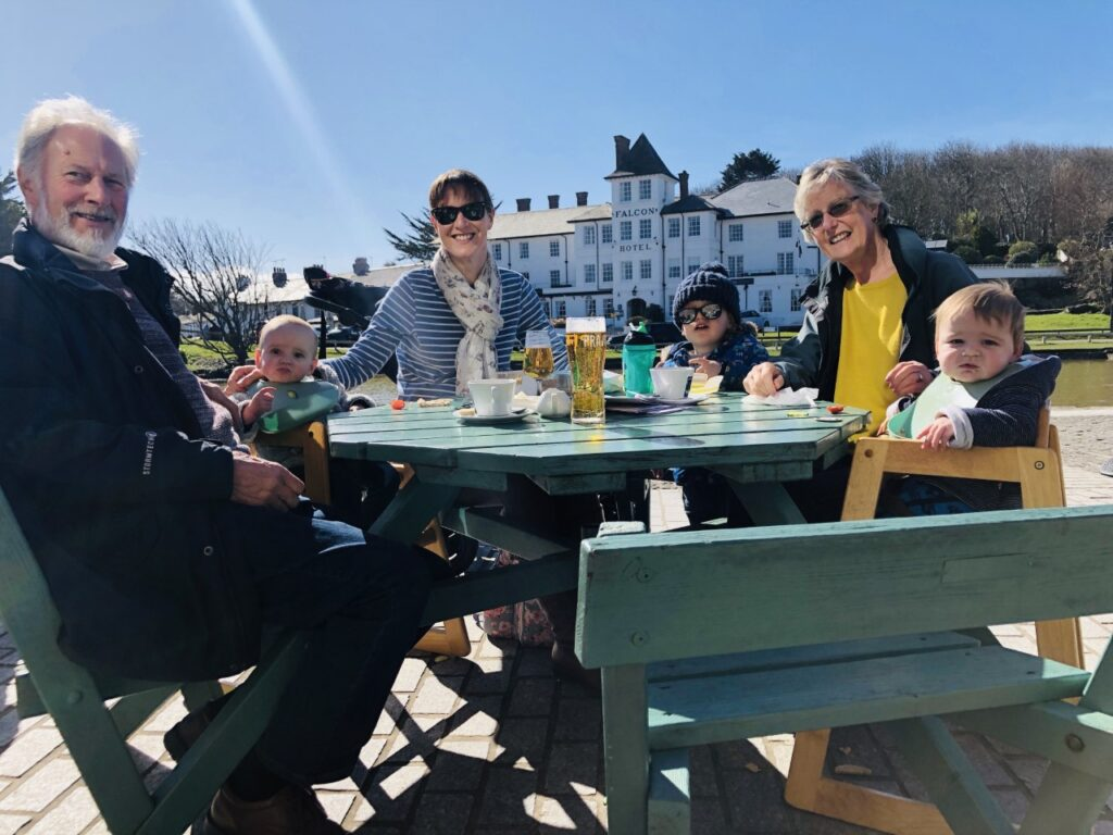 Family with young children and grandparents around an outdoor cafe table