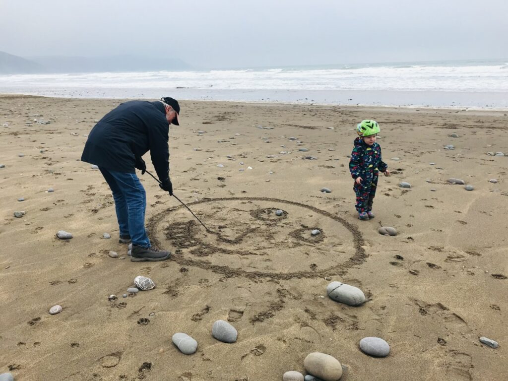 A grandad and two year old draw a face in the sand on the beach