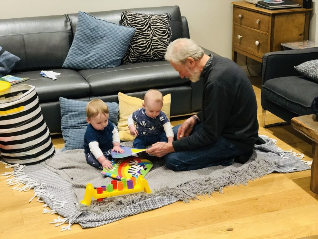 A grandad and twin nine month old twins play on the floor of a holiday home in north cornwall