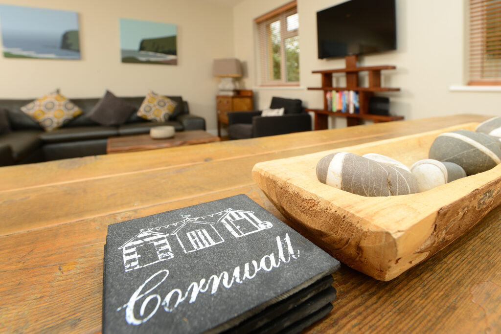 Slate coasters on a wooden table at Gwelmor holiday home in north cornwall