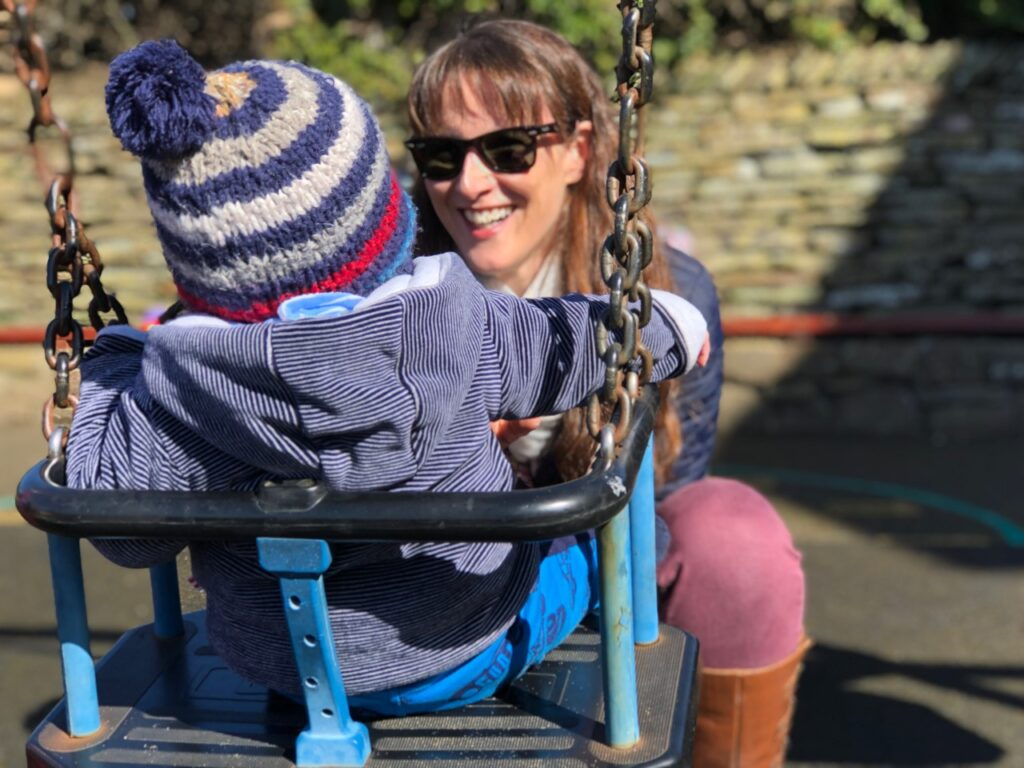Mum with dark hair and sunglasses crouched down in front of a baby in a swing