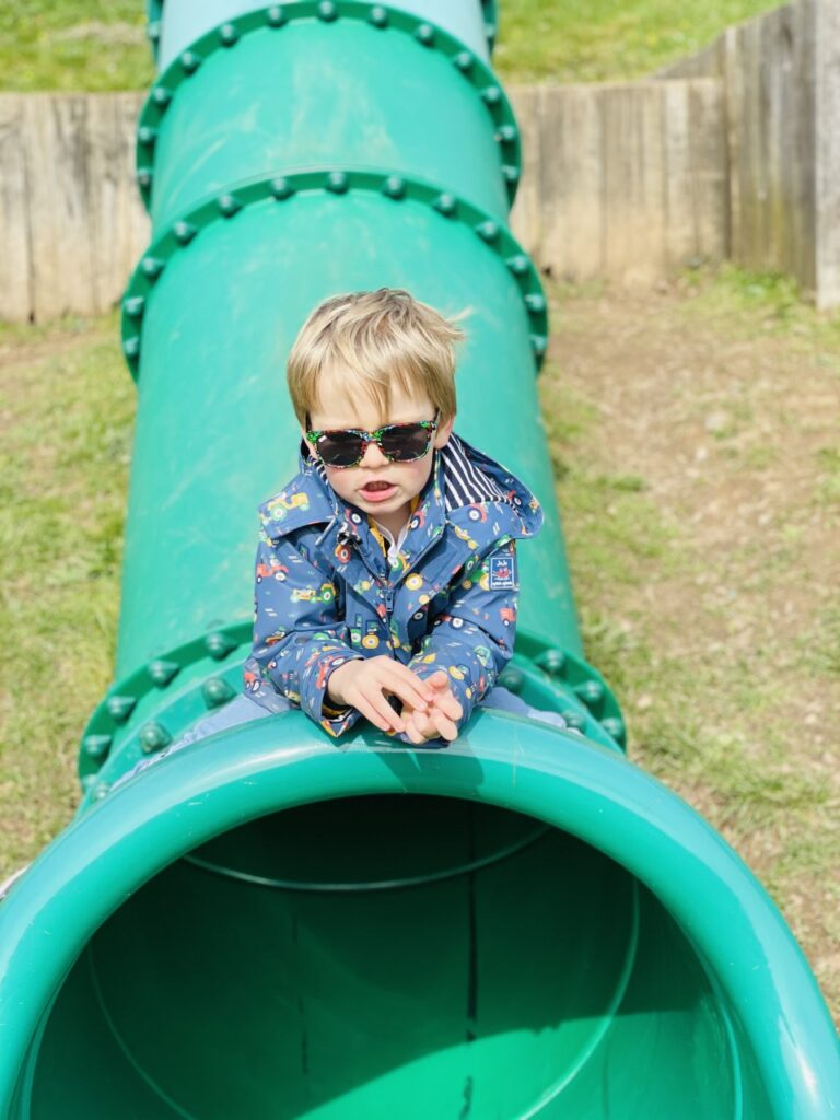 Three year old boy in a blue coat and sunglasses sits on the top of a green tube slide at the park