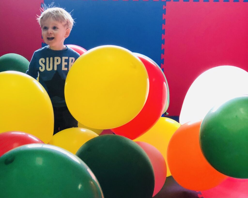 Two year old boy in a room of balloons at the Milky Way