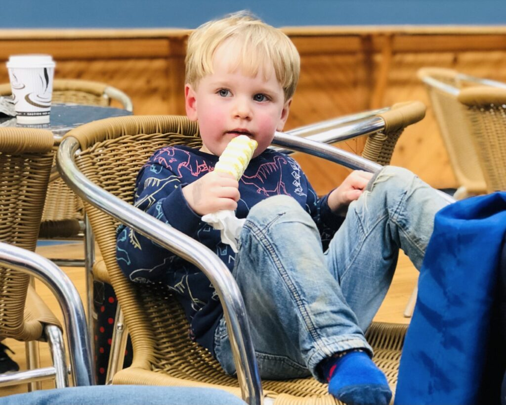 Blonde two year old boy in a chair eating a twister ice cream