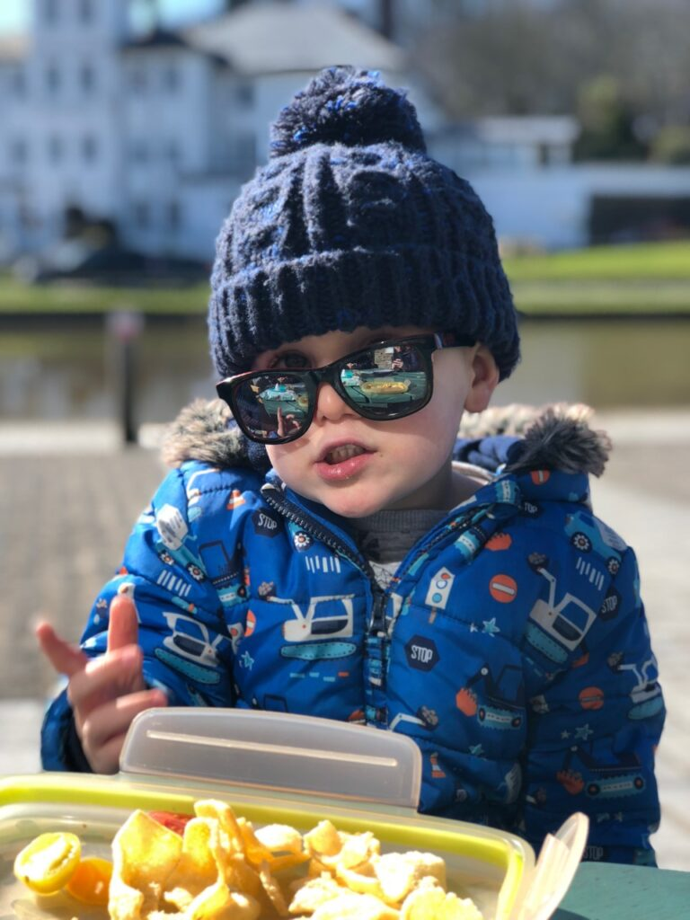 Toddler boy in woolly hat and sunglasses