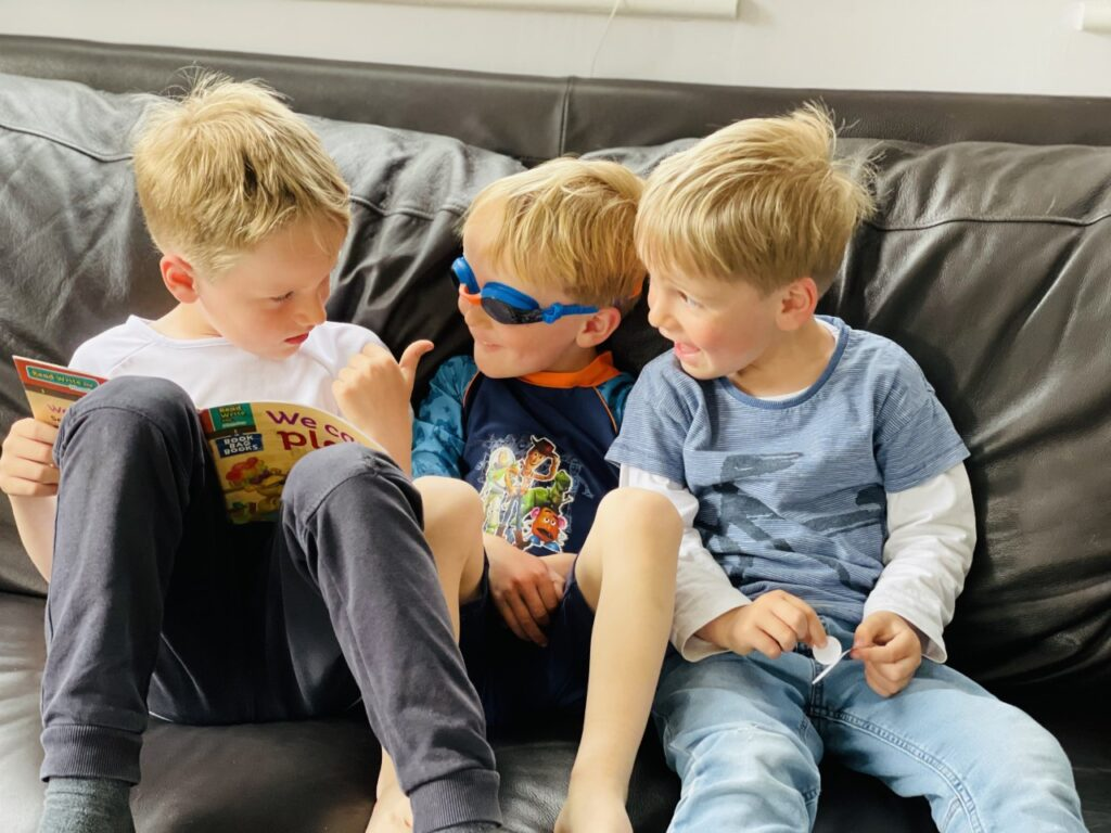Five year old big brother reads to his twin three year old brothers on the settee