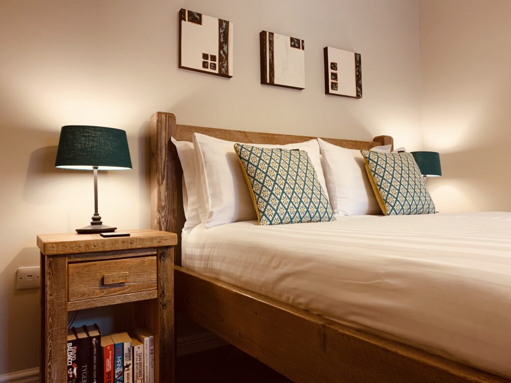 King size double bed and pine bedside table with lamp on