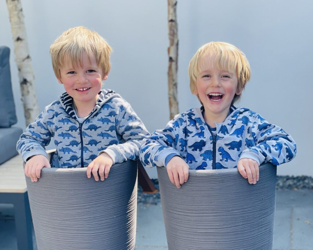 Twin three year old boys stand in plant pots in the garden playing during the pandemic