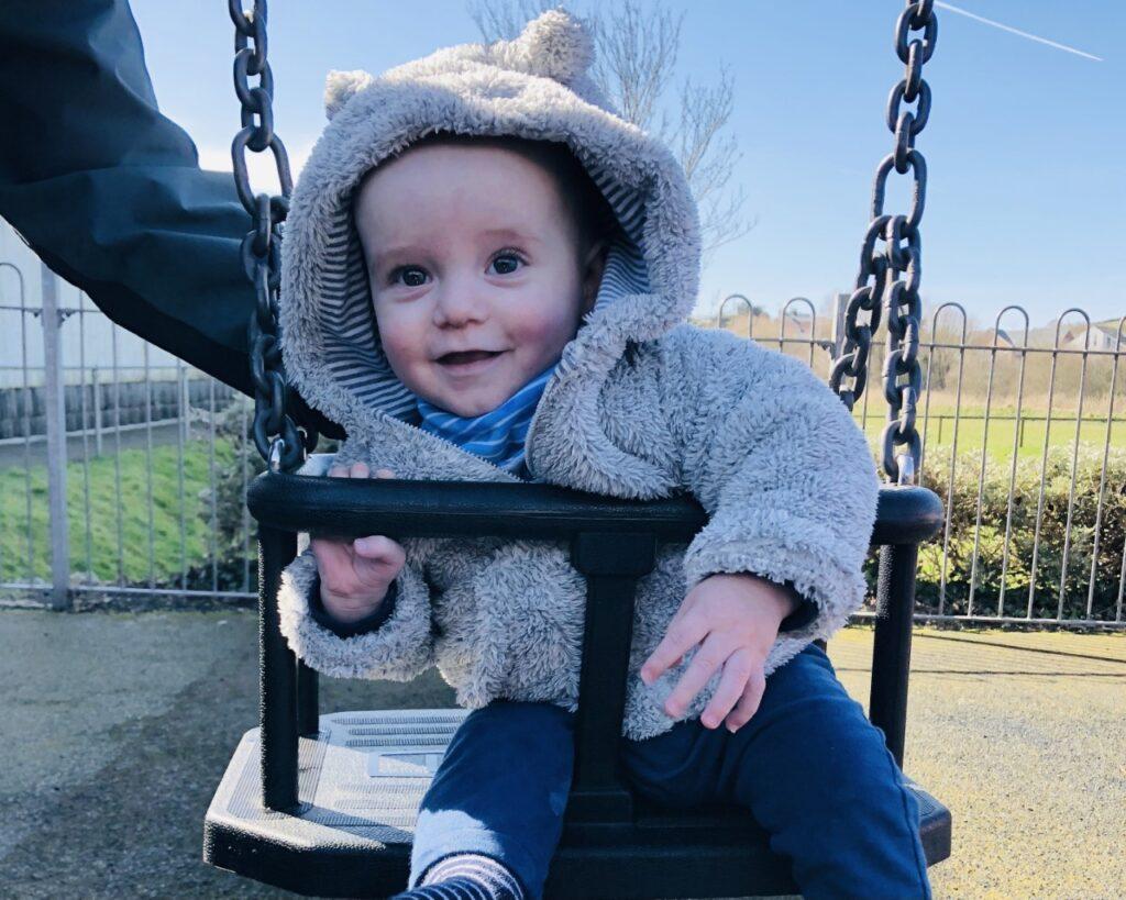 Nine month old baby in a bear fleece in a swing