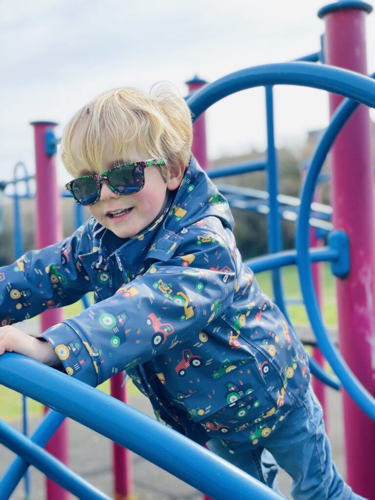 Blonde three year old boy wearing a blue coat and sunglasses on a climbing frame at the park
