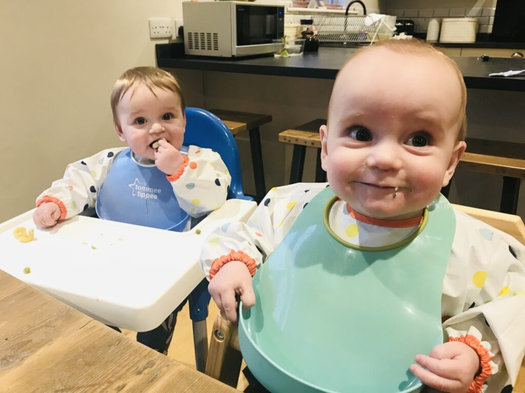Twin nine month old boys in highchairs at a table