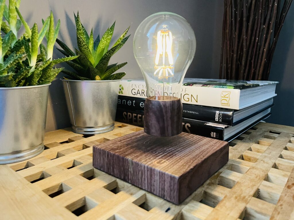 Volta levitating light bulb on a table next to books and cactus