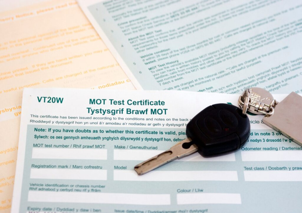 A car key on top of an MOT certificate on a table