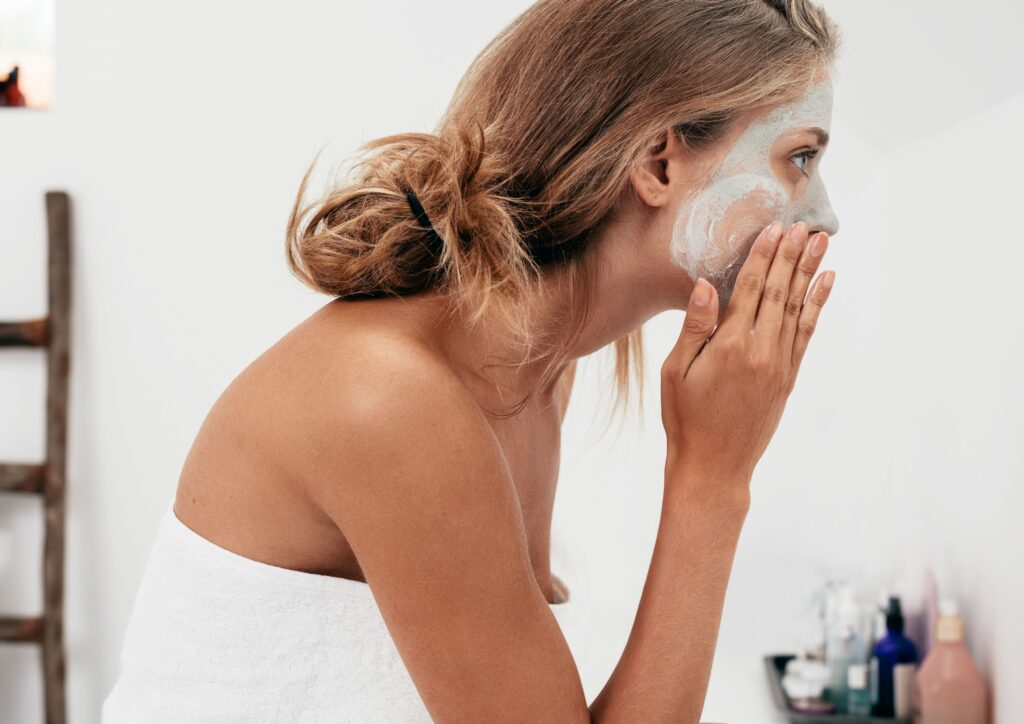 woman wearing a towel and hair tied back puts on a face mask as part of a self care routine