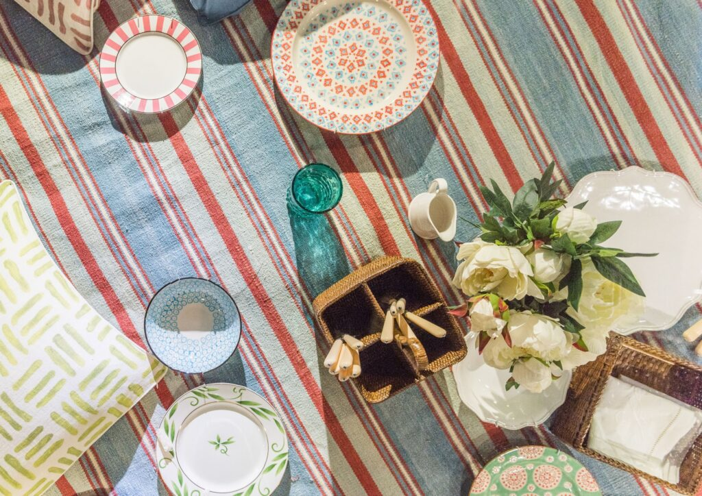 a stripy picnic rug with plates laid out