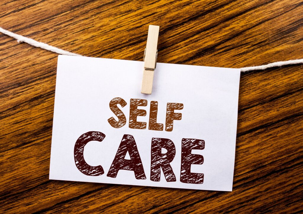 The words self care on a card hanging from a string with a clothes peg