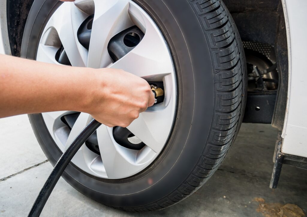 A tyre and hand checking pressure and adding air