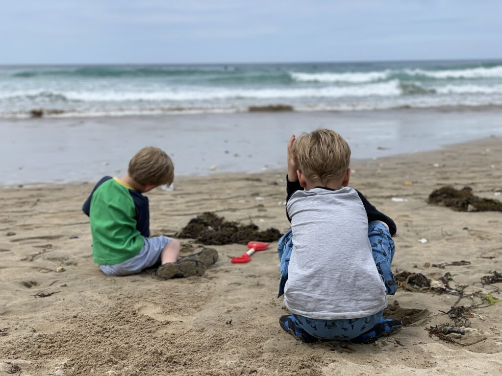 Six year old and four year old brothers build sandcastles on Fistral beach with their back to the camera and waves in the background