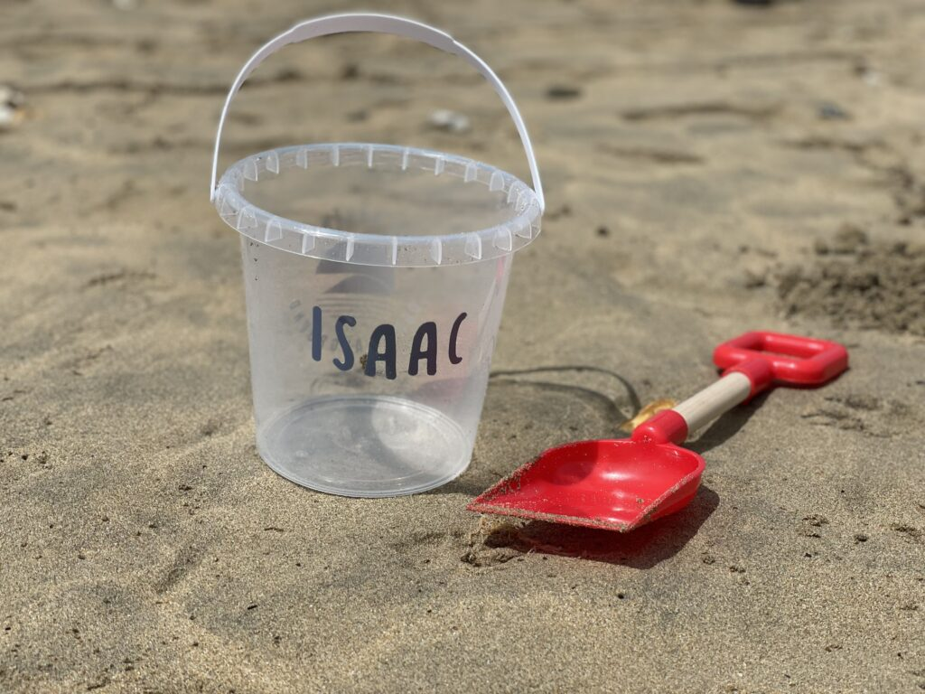 A personalised bucket and spade on a beach with the name Isaac on it.