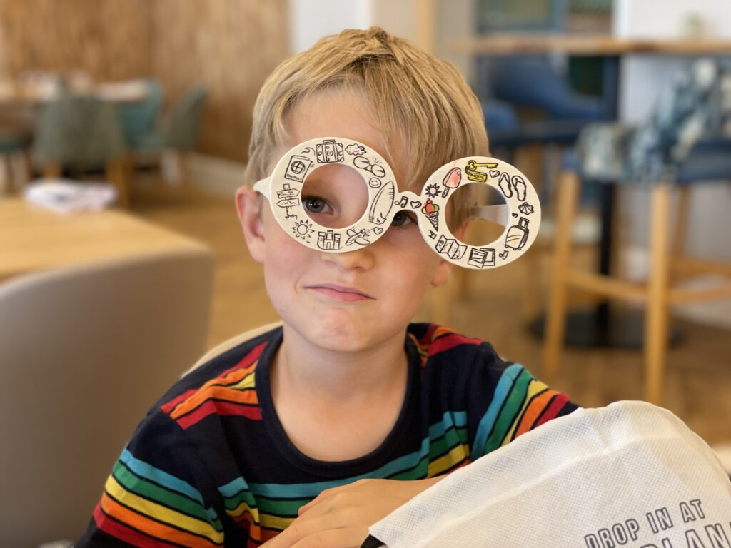 Six year old blonde boy wears funny oversized wooden glasses at a restaurant table
