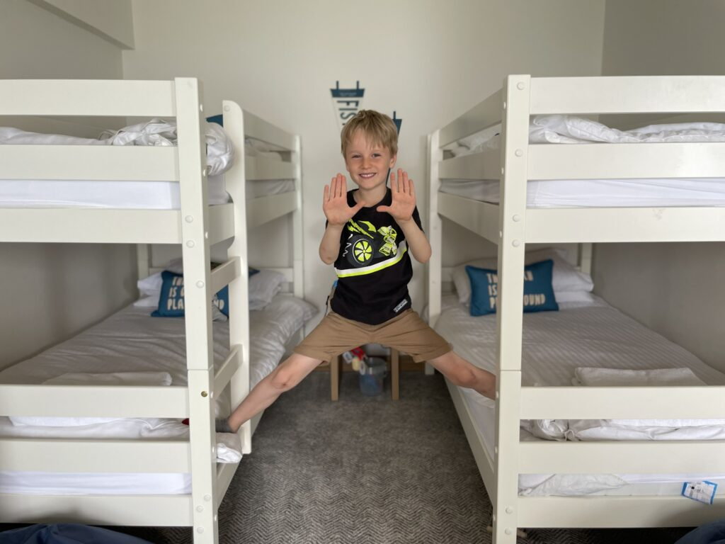 Six year old boy in black t shirt and shorts stands between two bunk beds