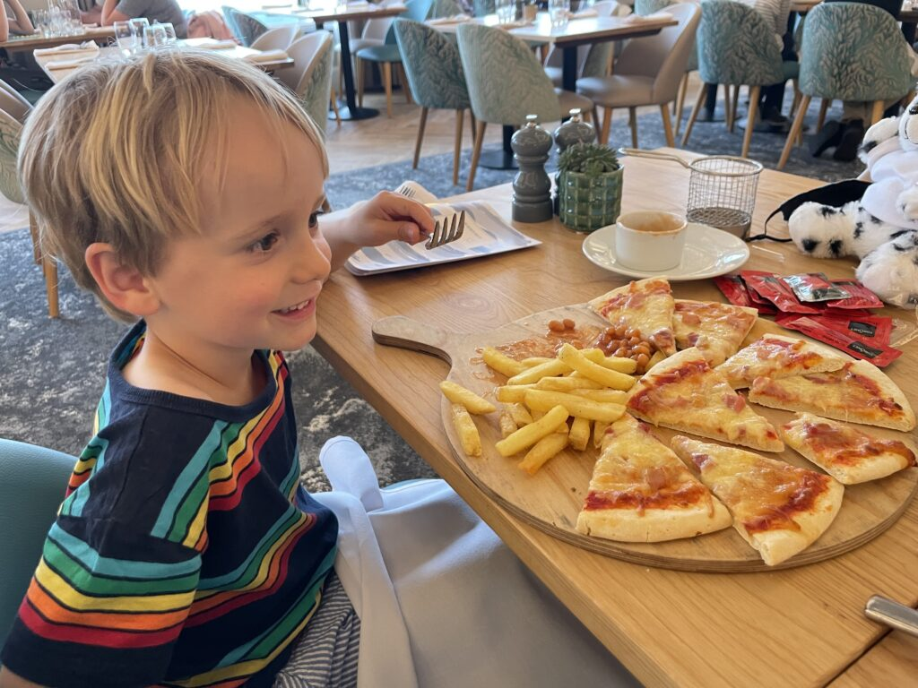 Four year old boy in stripy t shirt looks at a giant pizza in the restaurant of a family friendly hotel in Cornwall